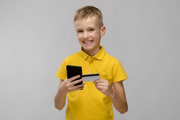 Pequeño muchacho rubio caucásico sonriente en camiseta amarilla con teléfono móvil y tarjeta de crédito