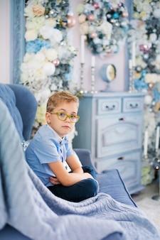 Pequeño muchacho rubio encantador en camisa azul con los vidrios grandes que se sientan en el sofá