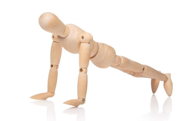 Pequeño muñeco de madera durante las flexiones