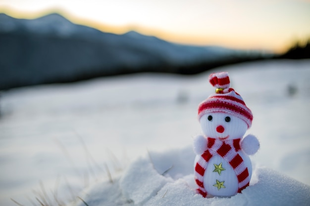 Pequeño muñeco de nieve de juguete divertido en gorro de punto y bufanda en nieve profunda al aire libre