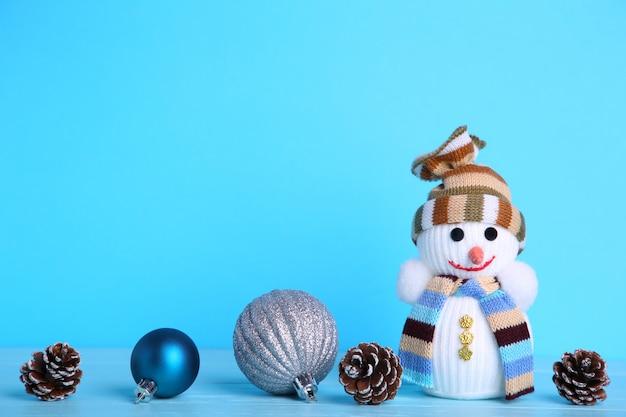 Pequeño muñeco de nieve de juguete sobre un fondo azul.