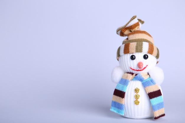 Pequeño muñeco de nieve de juguete sobre un fondo gris