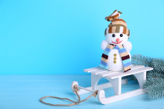 Pequeño muñeco de nieve con trineo blanco sobre fondo azul.