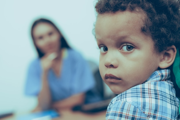 Pequeño niño afroamericano en recepción en el doctor