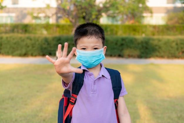 Pequeño niño asiático con máscara para proteger pm2.5 y mostrar gesto de detener las manos para detener el brote del virus corona.