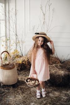 Pequeño niño encantador en vestido color de rosa y sombrero.
