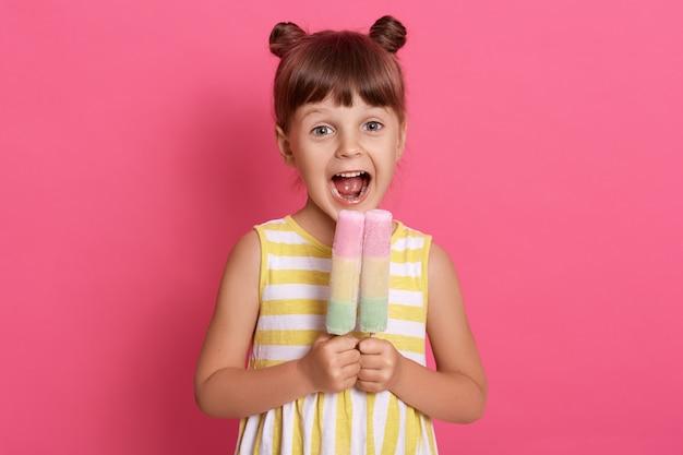 Pequeño niño europeo que muerde un helado de frutas, una niña encantadora con la boca muy abierta, vestida con ropa de verano, se ve feliz, divirtiéndose con un delicioso postre