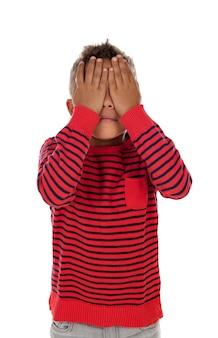 Pequeño niño latino cubriéndose los ojos.