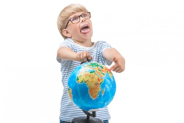 Pequeño niño lindo aislado en el fondo blanco que sostiene el globo. el alumno estudia geografía. chico lindo viaje. vacaciones familiares con niños