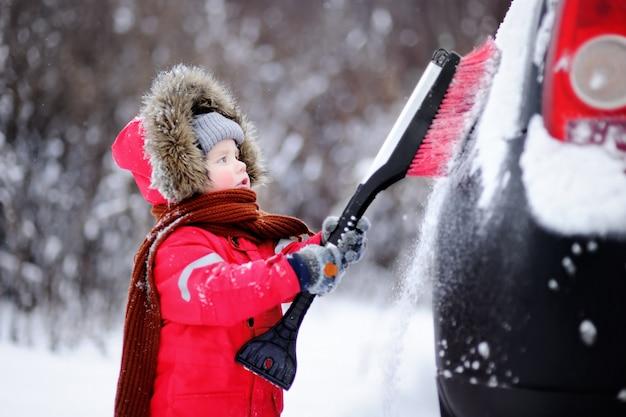 Pequeño niño lindo que ayuda a cepillar una nieve de un coche. niño pequeño usando una herramienta para limpiar el carro de los padres