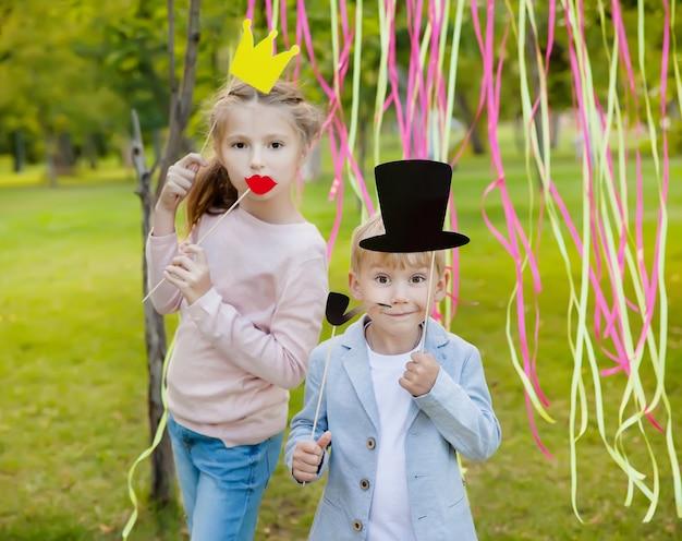 Pequeño niño y mujer posando con máscaras de papel en un cumpleaños