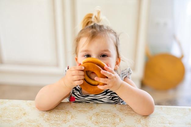Pequeño niño del niño que almuerza en la cocina soleada caliente. chica rubia con cola de caballo divertida jugando con dos sabrosos panecillos