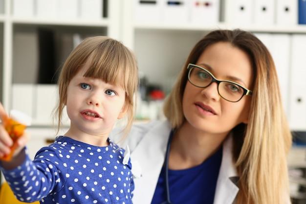 Pequeño niño en la oficina siendo revisado por el médico