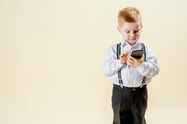 Pequeño niño pelirrojo en un traje de negocios con un teléfono en la mano se apresura a una reunión en un traje de negocios, negocios, mini jefe