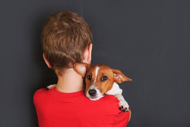 Pequeño niño que abraza el gato lindo russell del perrito.