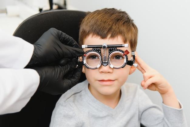Pequeño niño serio sentado en la oficina de la silla de examen de la vista. el doctor toma lentes para lentes especiales.