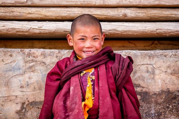 El pequeño niño sonriente de monjes budistas novatos está rezando en el monasterio de boudhanath