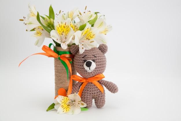 Pequeño oso pardo con flores blancas, juguete de punto, hecho a mano. amigurumi.