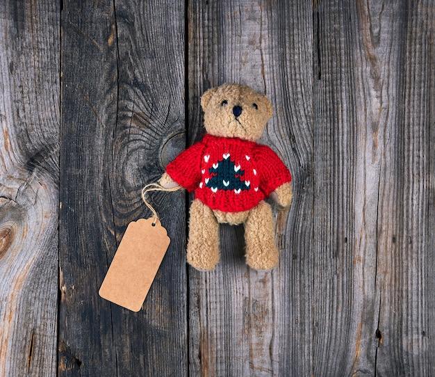 Pequeño oso de peluche viejo marrón con una etiqueta de papel en blanco