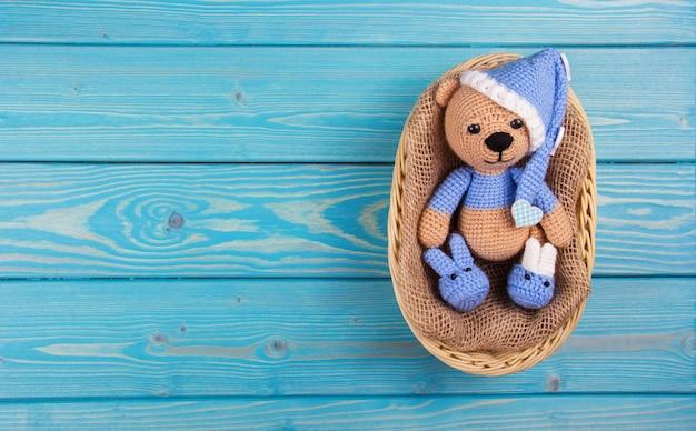 Pequeño oso de punto tumbado en la cesta sobre fondo de madera azul