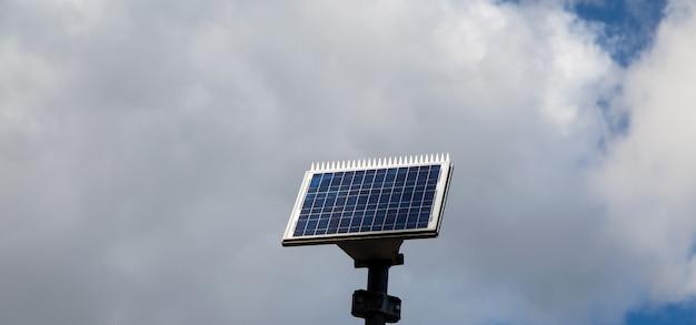 Pequeño panel solar con fondo de nubes