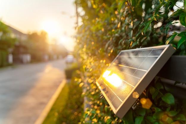 Pequeño panel solar en pared con luz solar. energía verde en el concepto de hogar.