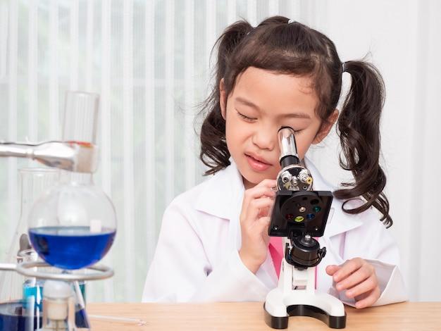 Pequeño papel asiático lindo de la muchacha que juega a científico en laboratorio de ciencia y que aprende utilizar el microscopio.