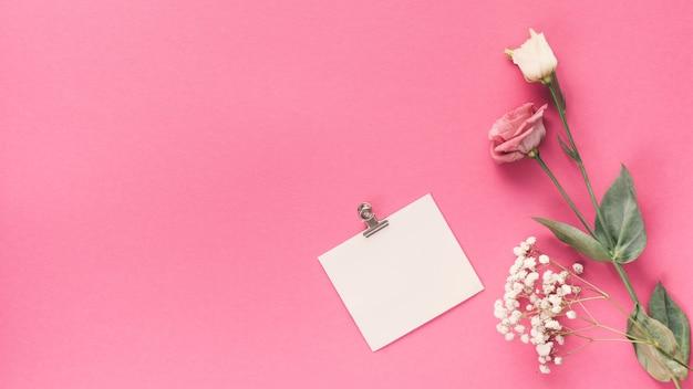 Pequeño papel en blanco con diferentes flores en la mesa