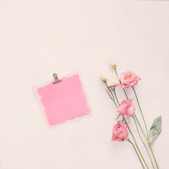 Pequeño papel en blanco con flores brillantes en la mesa