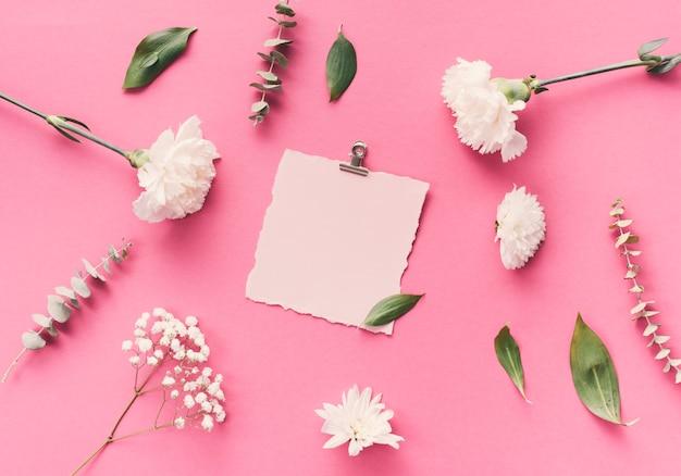 Pequeño papel en blanco con flores en la mesa