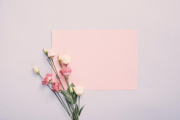 Pequeño papel con flores color de rosa en mesa de luz