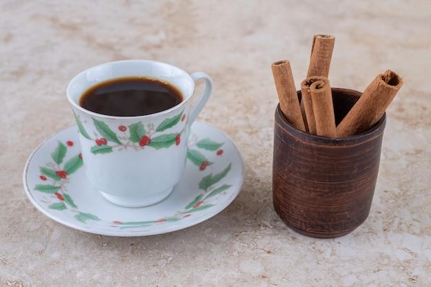 Un pequeño paquete de ramas de canela y una taza de café.