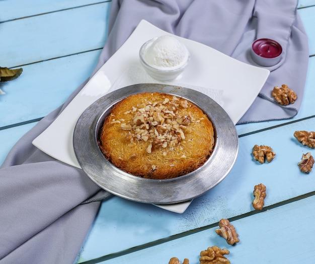 Un pequeño pastel con nueces y helado.