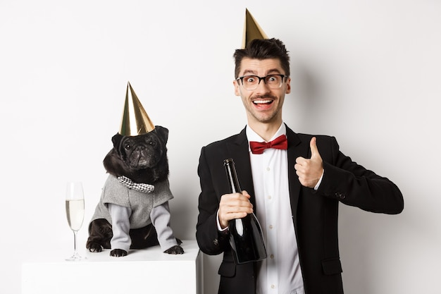 Pequeño perro negro con sombrero de fiesta y de pie cerca de un hombre feliz celebrando las vacaciones, propietario mostrando el pulgar hacia arriba y sosteniendo una botella de champán, fondo blanco.
