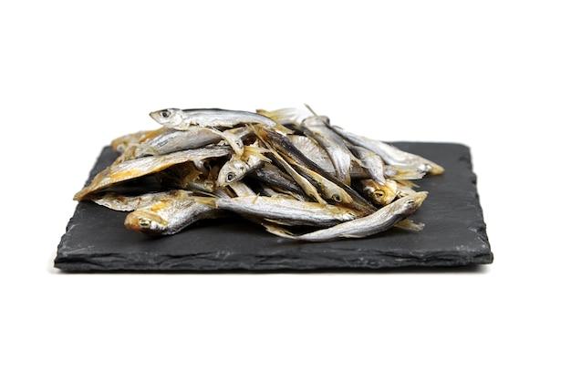 Pequeño pescado seco en tablero de pizarra negro aislado en blanco