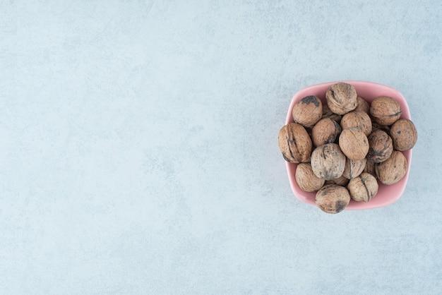 Un pequeño plato rosa lleno de nueces sobre fondo de mármol. foto de alta calidad