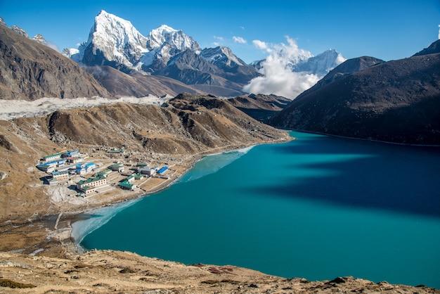 Pequeño pueblo cerca de un cuerpo de agua azul rodeado de hermosas montañas.