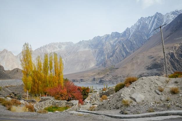 Pequeño pueblo en passu contra la cordillera nevada en la temporada de otoño, pakistán.