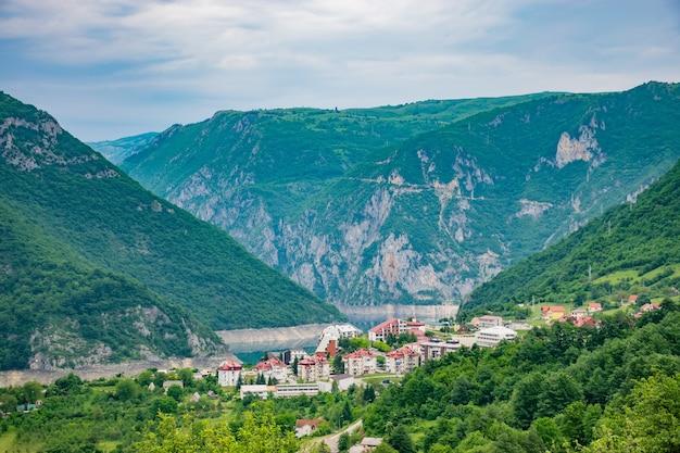 Un pequeño pueblo está ubicado en la orilla de un pintoresco lago entre las altas montañas.