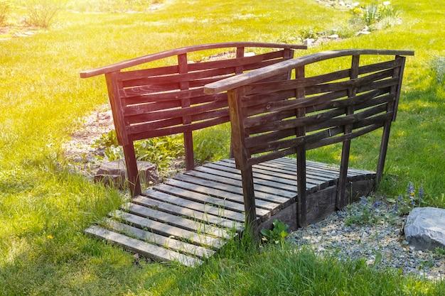 Pequeño puente de madera en un hermoso jardín verde.