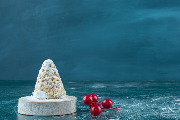 Un pequeño racimo de bayas navideñas junto a un pastel recubierto de vainilla sobre azul.