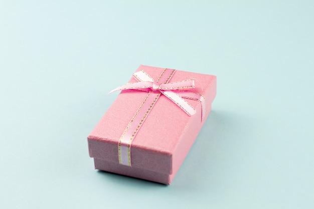 Pequeño regalo en un fondo en colores pastel, primer. caja de regalo con un lazo