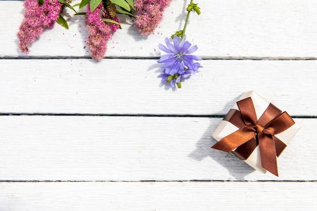 Pequeño regalo con vista superior de flores.