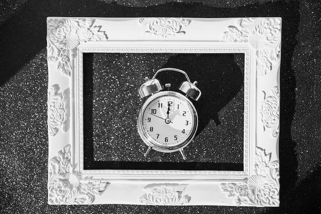 Pequeño reloj en marco sobre mesa