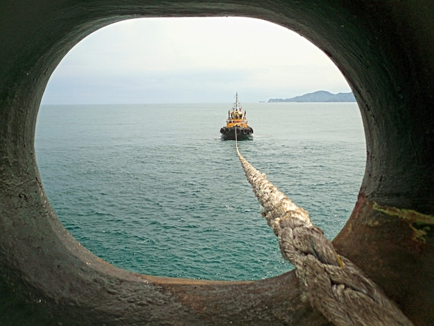 Un pequeño remolcador arrastra a un gran buque al puerto. vista desde el ojo de buey