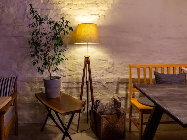 Pequeño restaurante interior, lámpara, pared de piedra blanca y planta