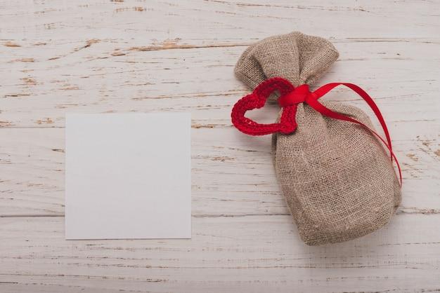 Pequeño saco marrón con un lazo rojo y un papel en blanco