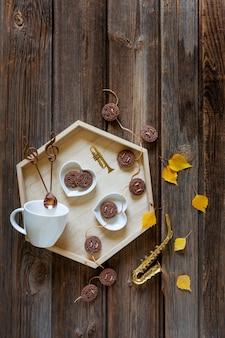 Pequeño saxofón dorado y hojas de otoño y una bandeja con taza y galleta. otoño