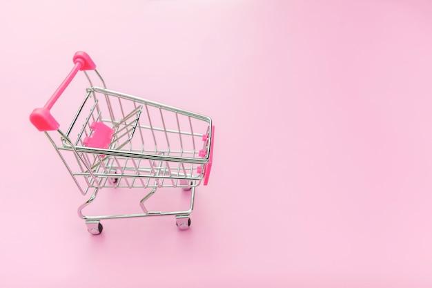 Pequeño supermercado carrito de compras para compras aislado sobre fondo rosa