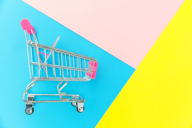 Pequeño supermercado supermercado carrito de empuje de juguete aislado sobre fondo azul pastel amarillo y rosa pastel colorido